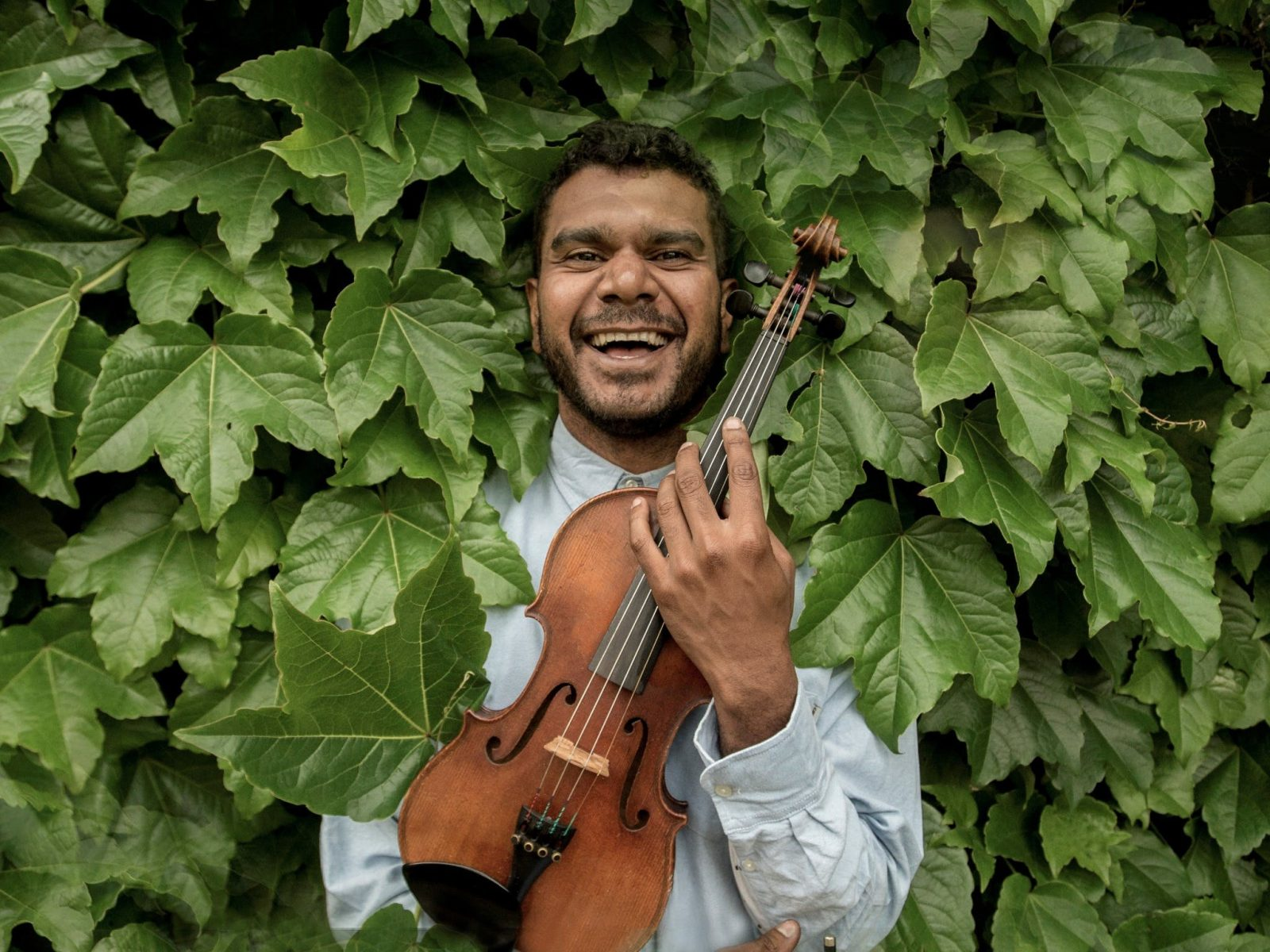 Man stands in leafy bushes smiling and holding a violin