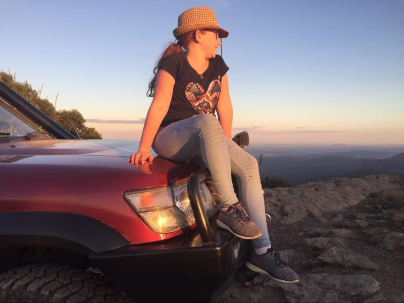 girl looking at sunset in car bonnet