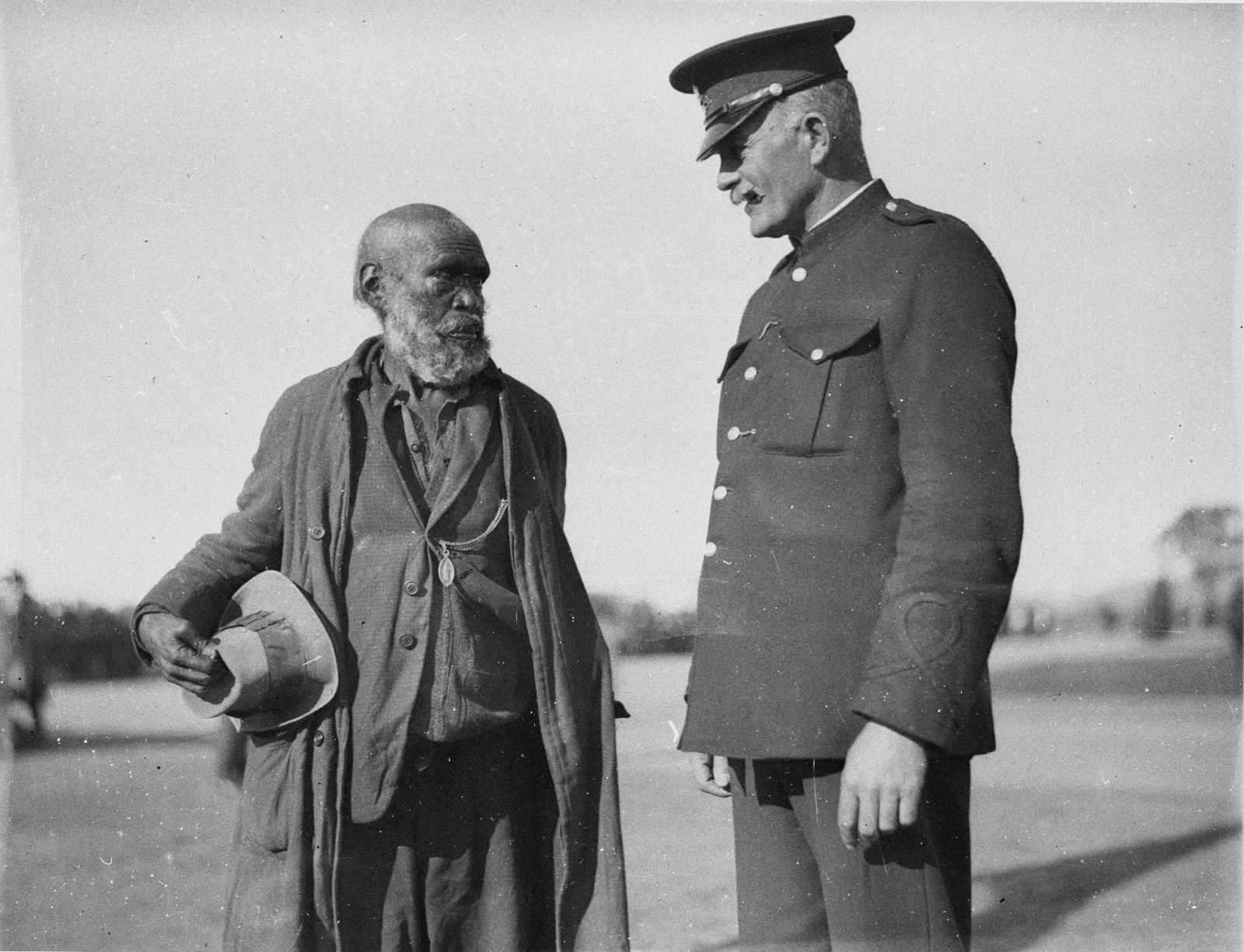 A police officer speaking to an Aboriginal man