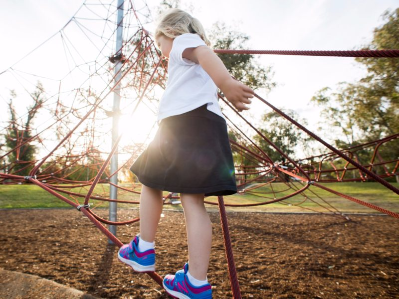 Young girl on a rope climbing frame