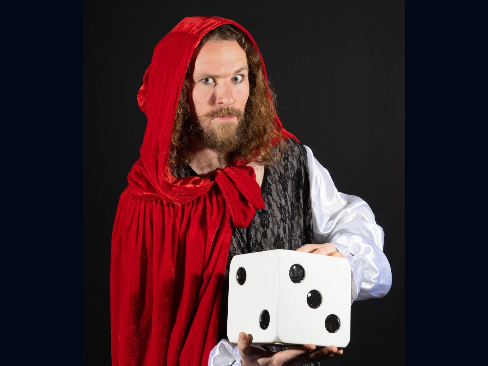 Man in red robe holding an oversized die