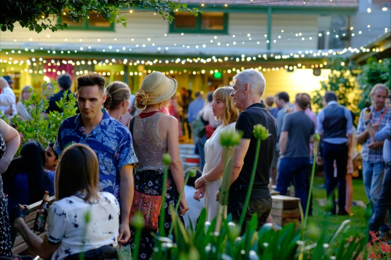 People milling in the Gorman Courtyards at twilight, surrounded by leafy foliage and fairylights