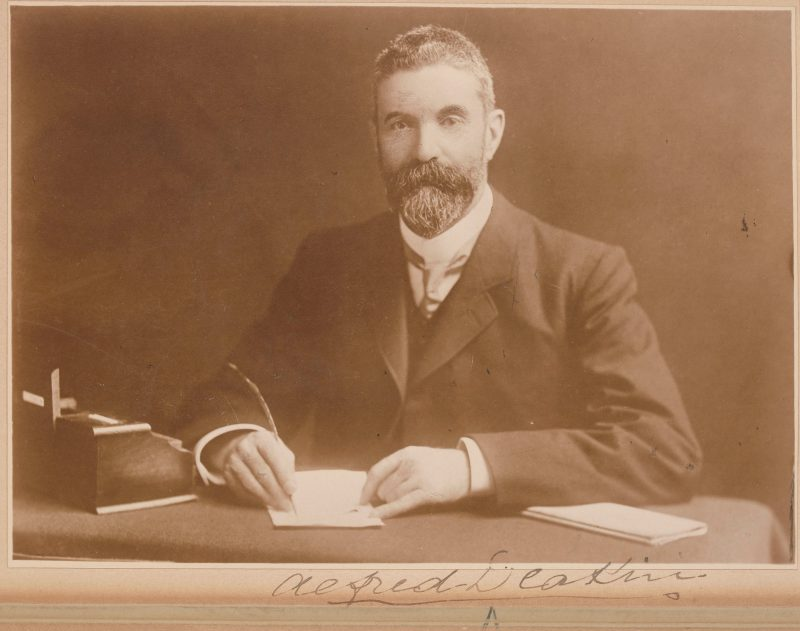 A sepia photograph of former Prime Minister Deakin. He sits at a desk, writing on paper with a quill