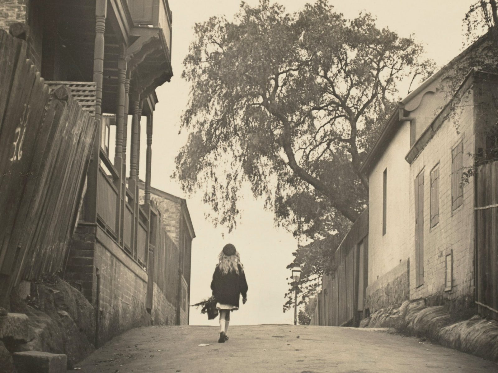 Young girl walking down street in 1910