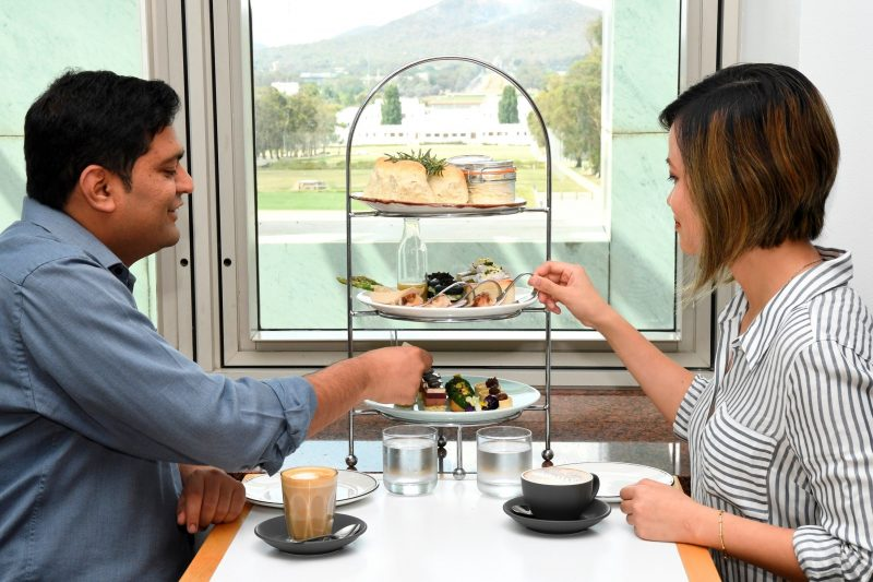 A couple sits in the Queen's Terrace Cafe enjoying High Tea