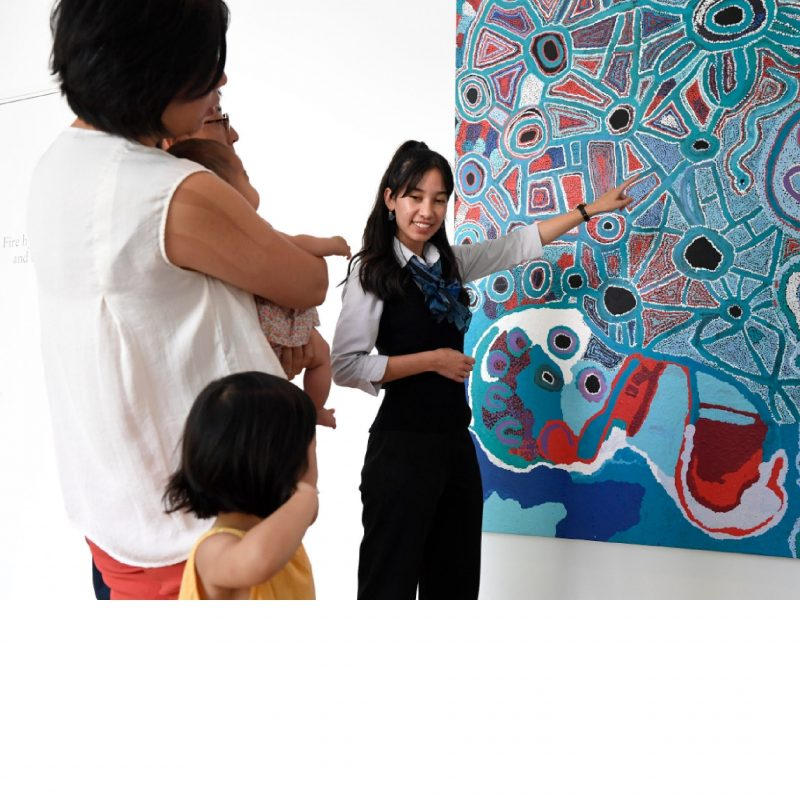 A tour guide talks about an artwork to a family