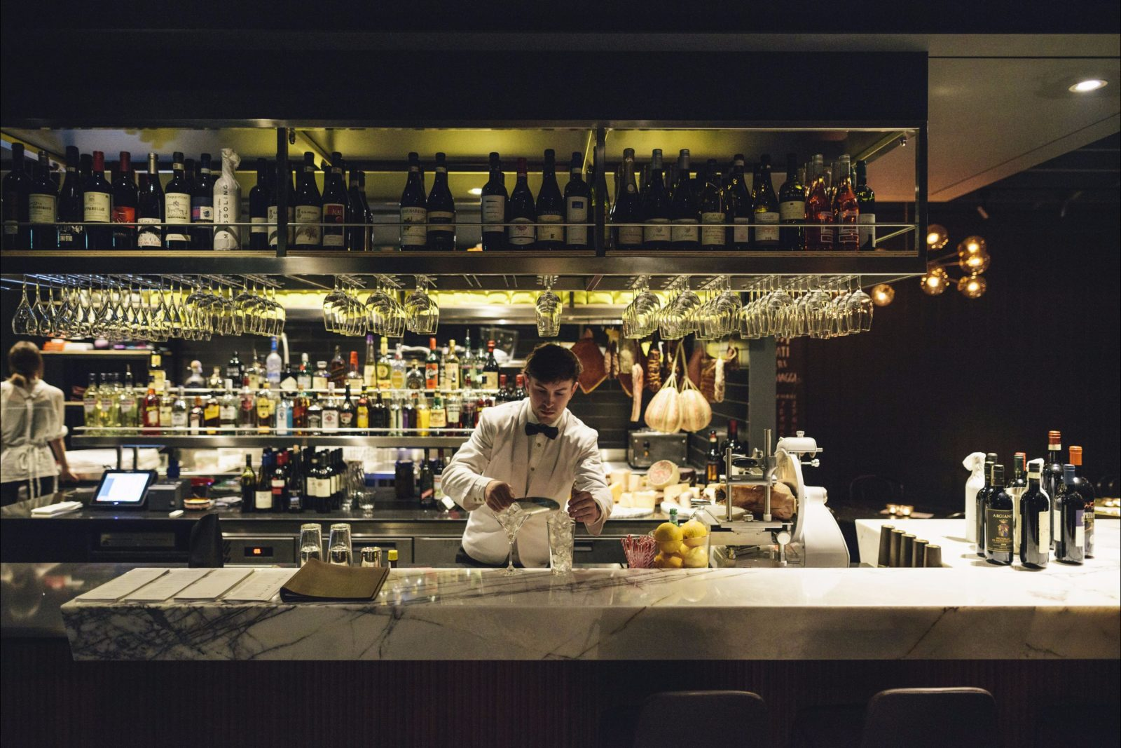 Barman pouring drinks at a marble bar