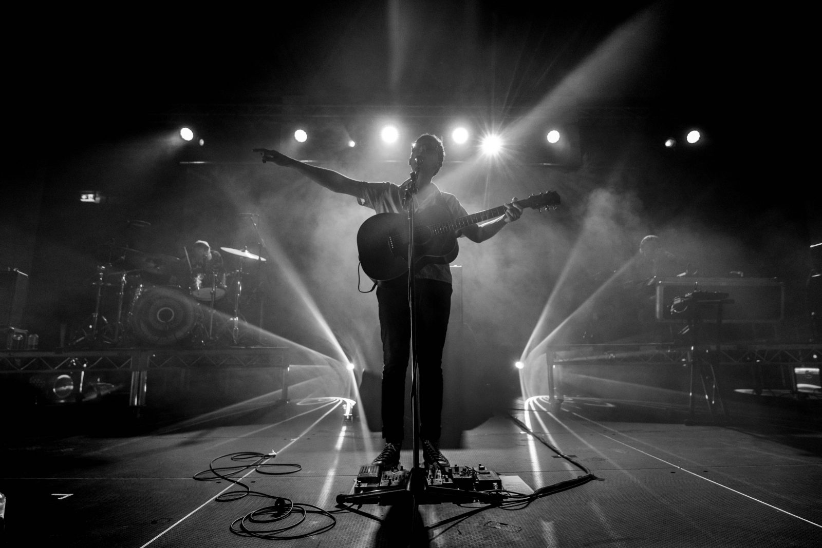 photograph shows singer of Ball Park Music silhouetted on stage