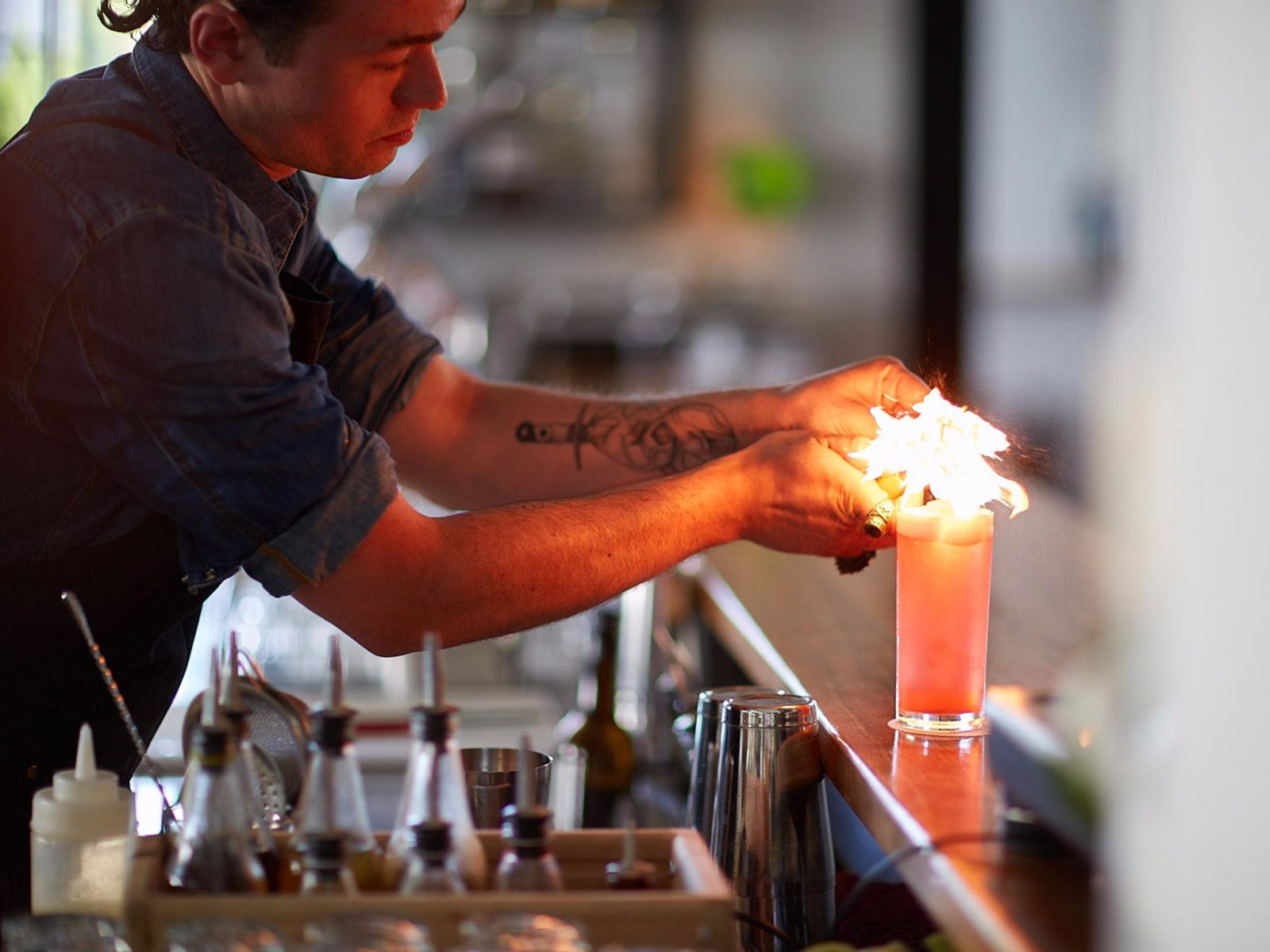 Barman lighting a cocktail on the bar