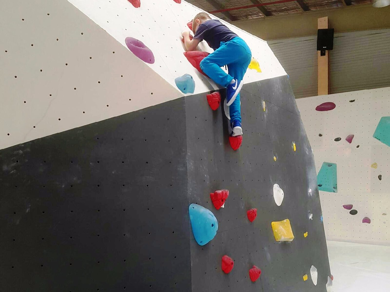 Young boy climbing on a bouldering wall