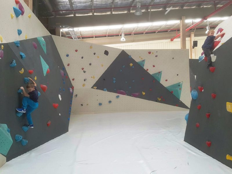 Two young boys on separate climbing walls