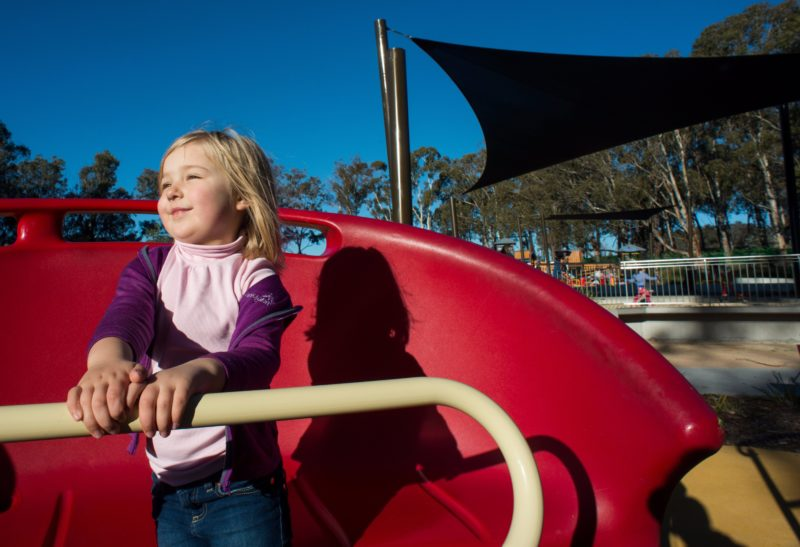 Girl on a spinning piece of play equipment in the Boundless Playground