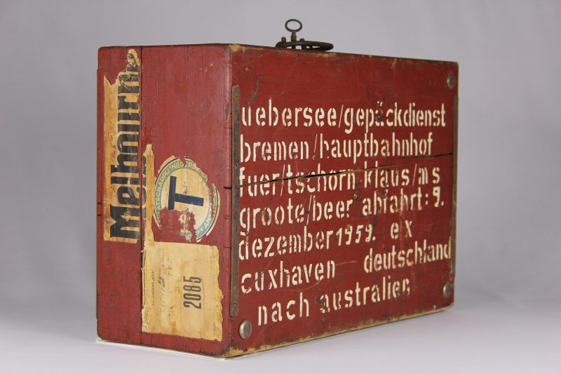 A travel case orange in colour with writing and signage on the side