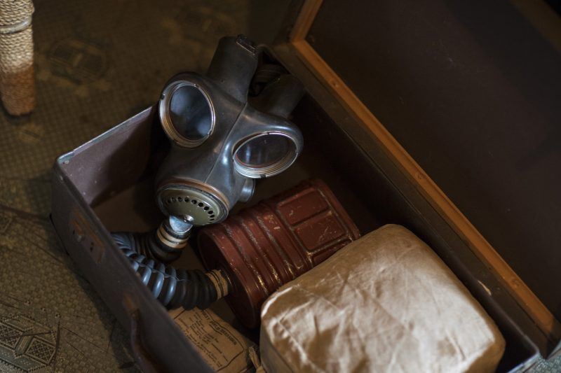 An open suitcase containing a WWII gas mask