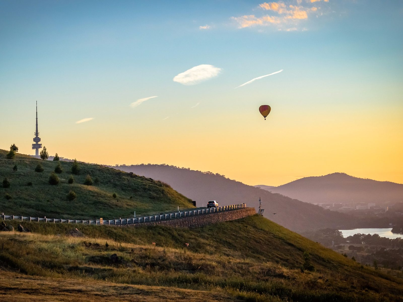 Hot air balloon over hills with view to the city centre