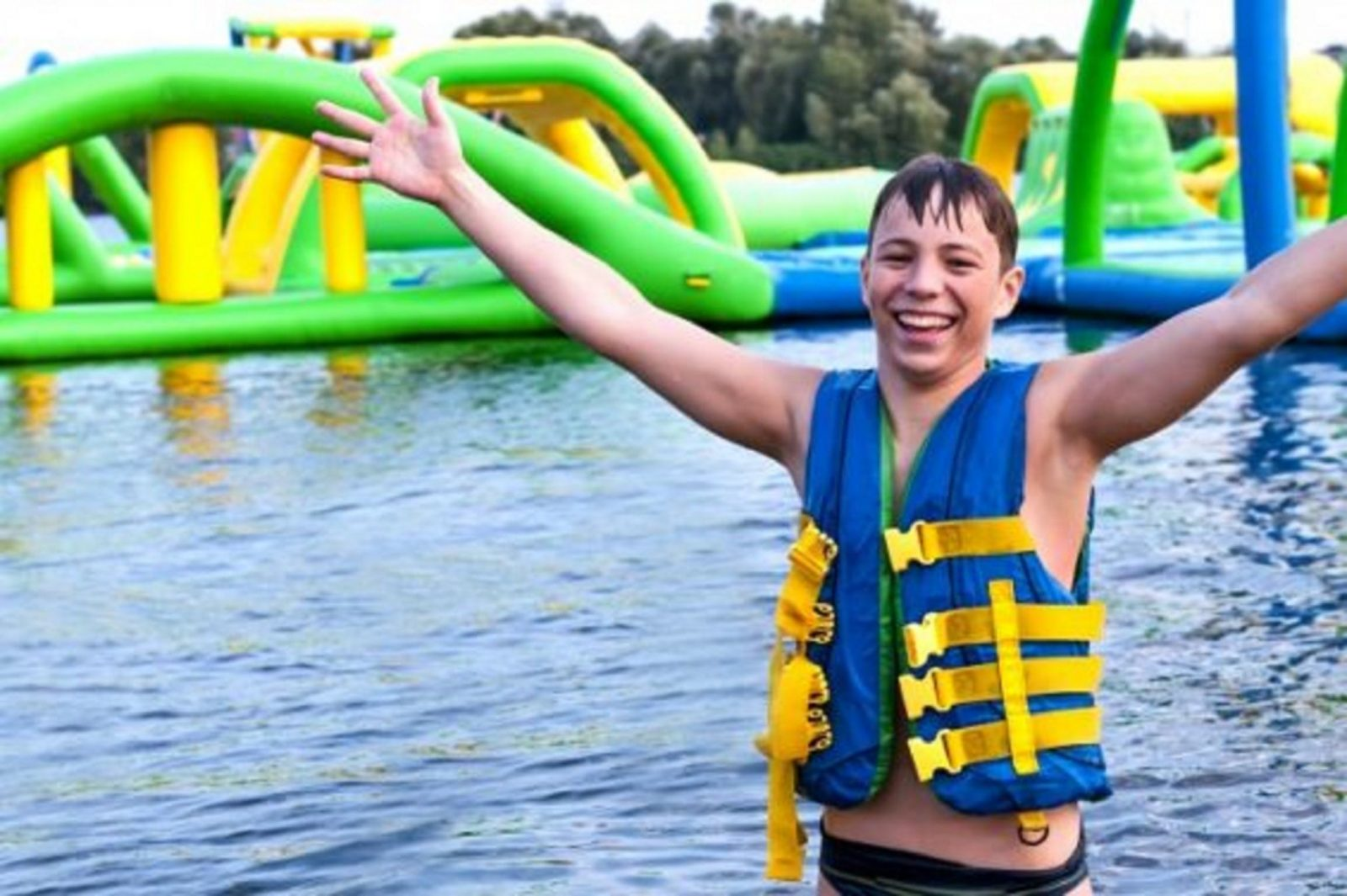 Child at waterpark with arms in the air