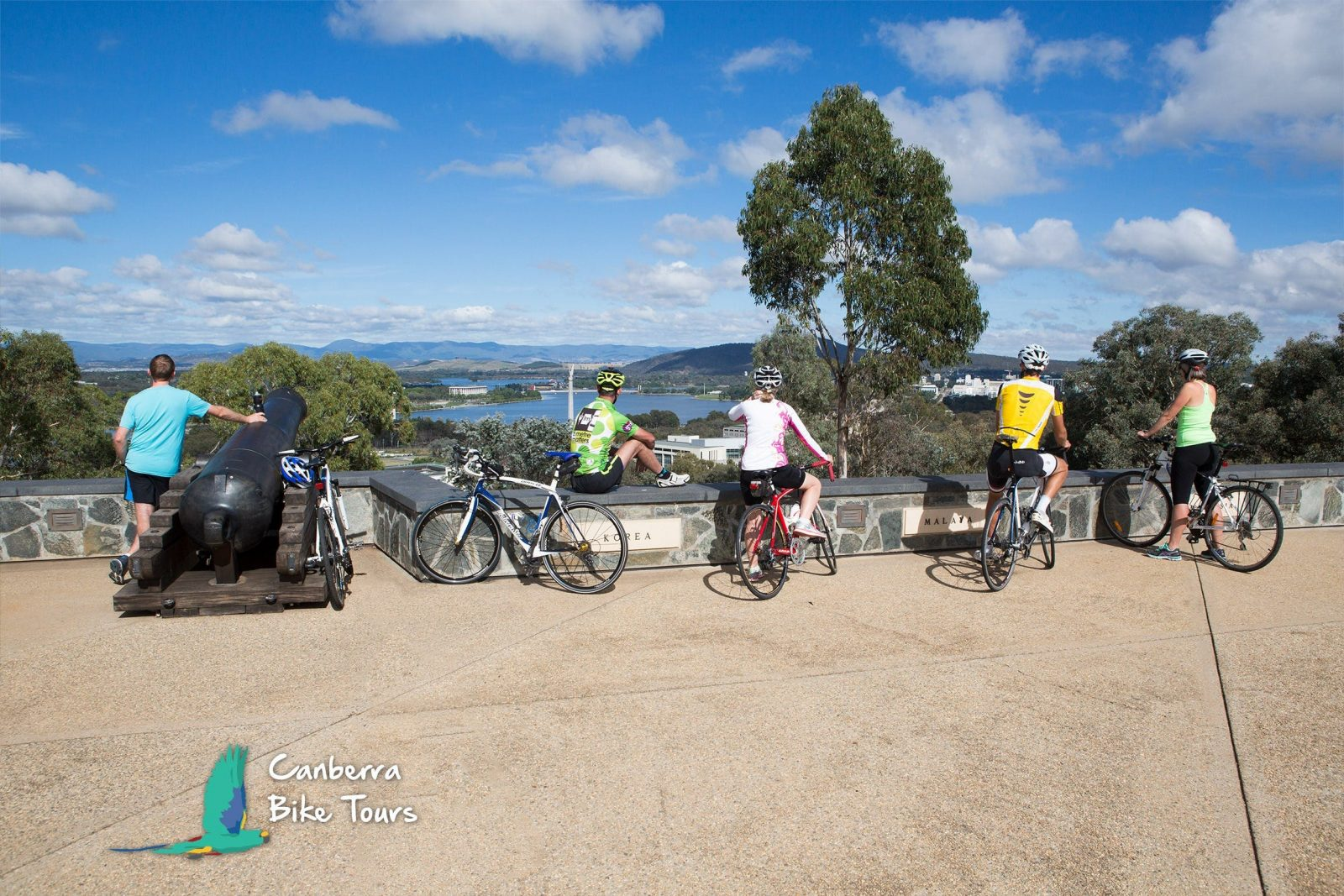 Five cyclists on top of Mt Pleasant admire the view of Canberra.