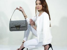 Woman dressed in white poses with handbag