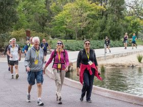 Group of people walking around Lake Burley Griffin.