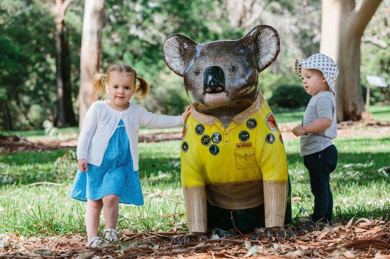 children with koala sculpture