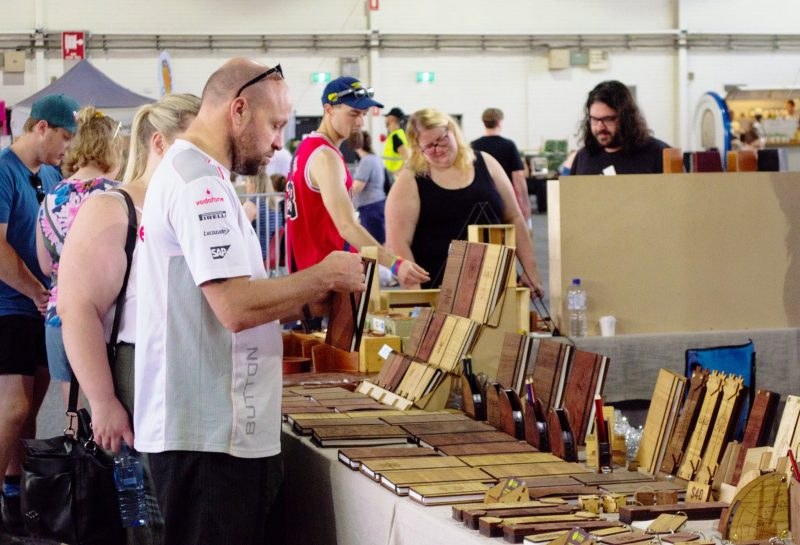 Shoppers at CBRmade Etsy Made Local market buying handmade wooden notebooks