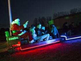 Santa riding the train with children and Christmas lighting
