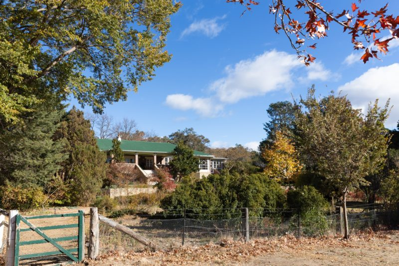 view of a heritage listed homestead amidst an autumnal garden