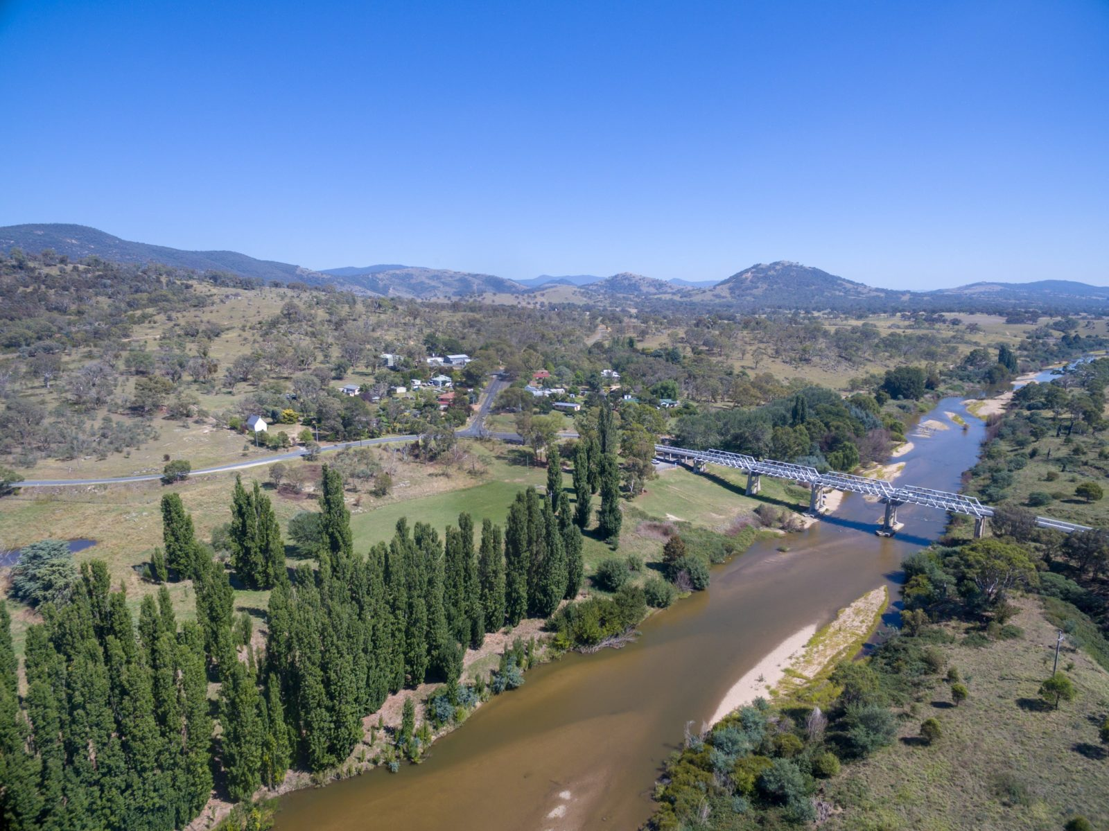 aerial photo of the Murrumbidgee river with the Tharwa Bridge crossing it
