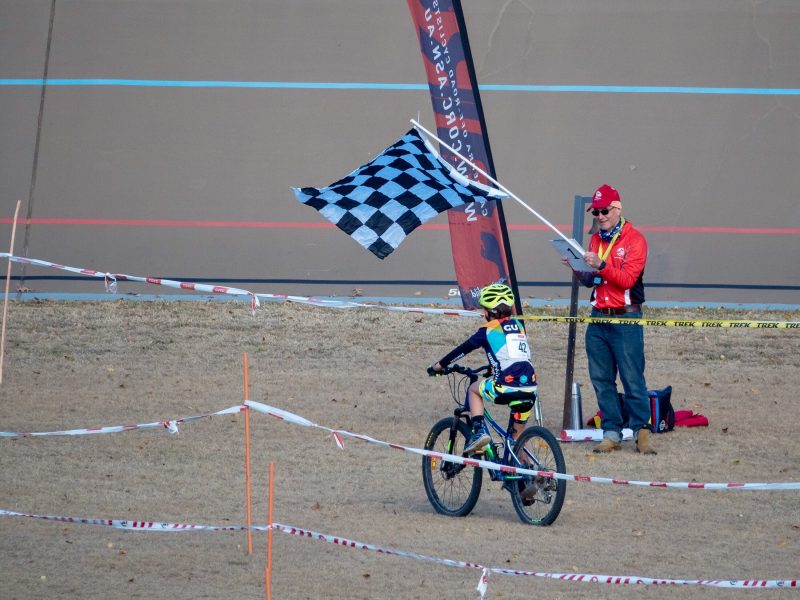 A young rider crosses the finish line under a chequered flag
