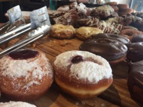 Array of handmade doughnuts on a wooden board