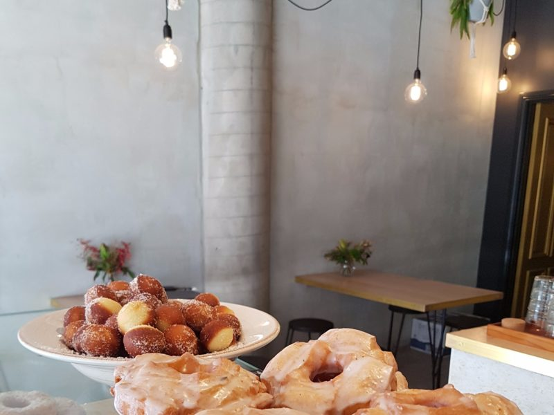 Doughnuts and doughnut balls on top of a display counter. Modern concrete walls and exposed lights