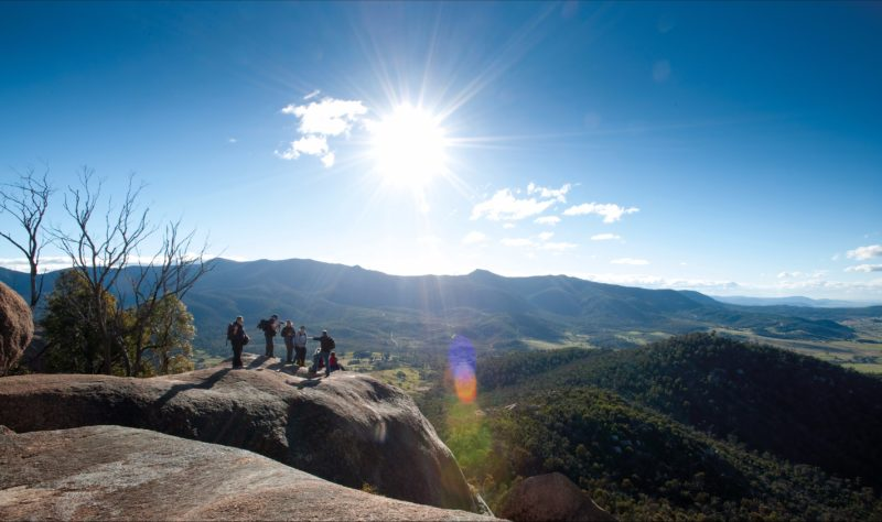 Small group of people looking out over magnificent views of the valley and mountain ranges