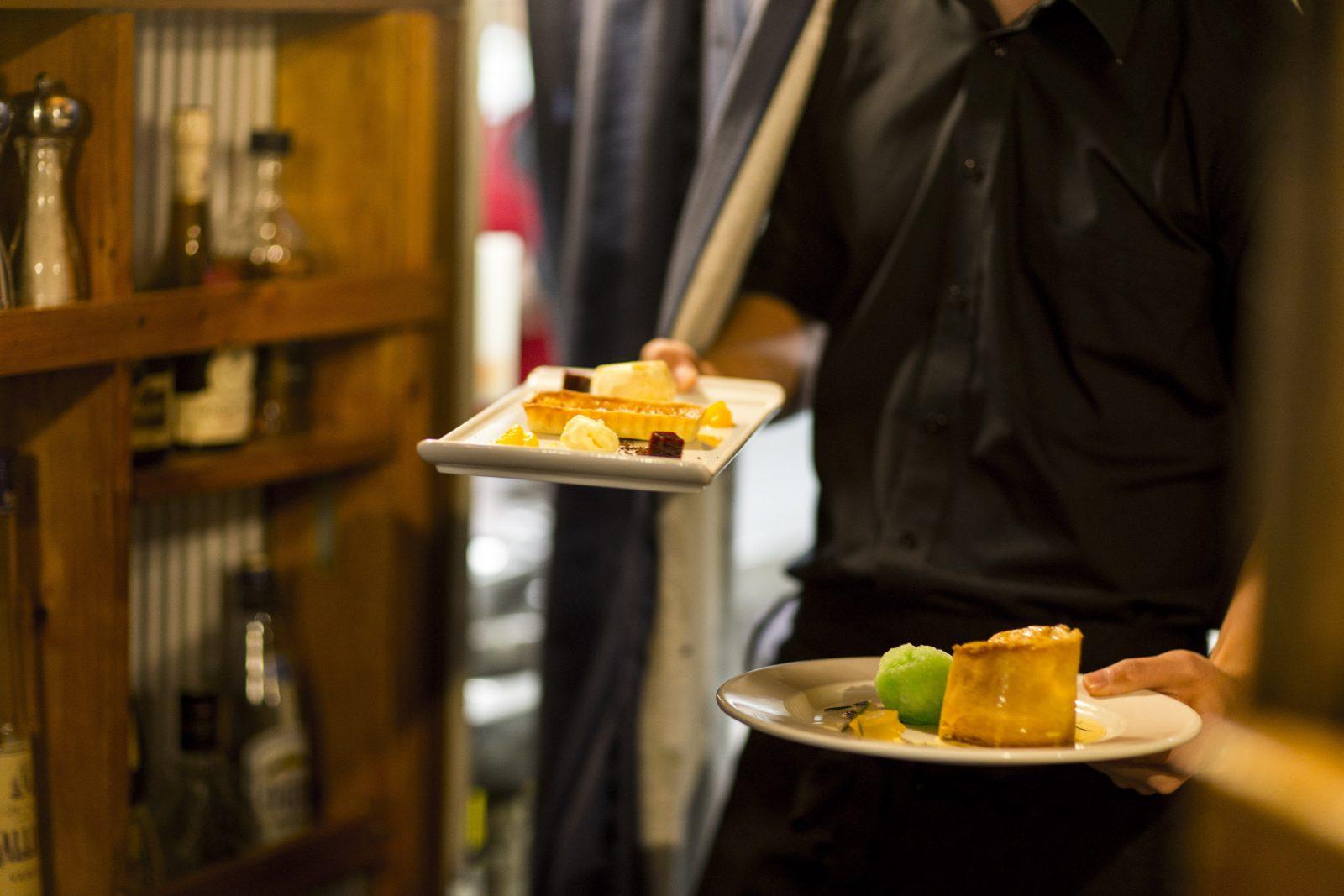Waiter carrying two plates of desert