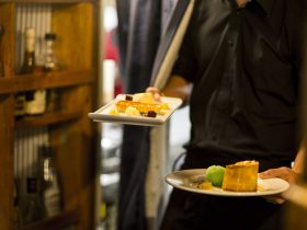 Waiter carrying two plates of desert