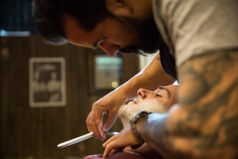 Barber shaving a man with a straight razor