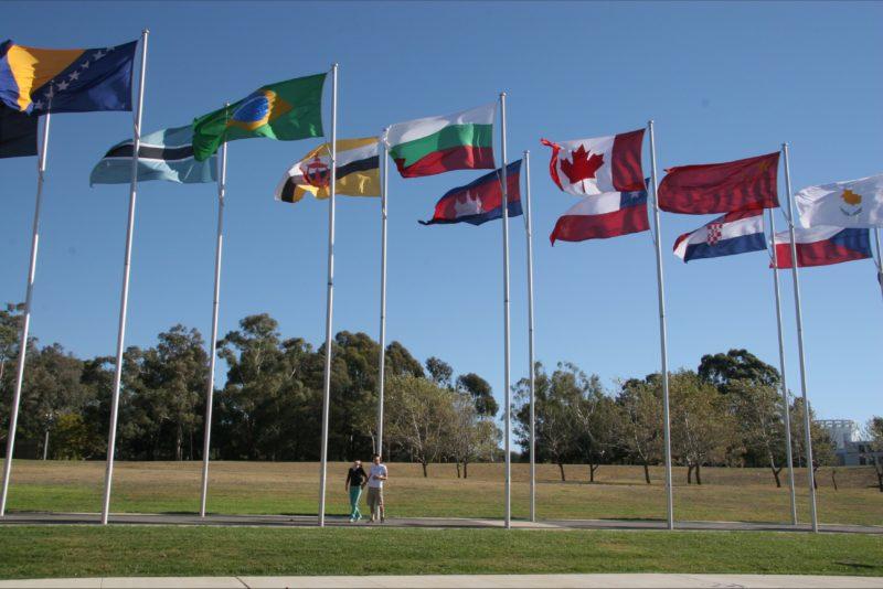 Couple walking underneath international flags