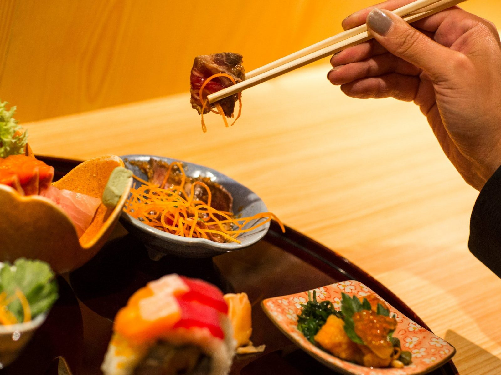 Hand holding japanese food in chopsticks