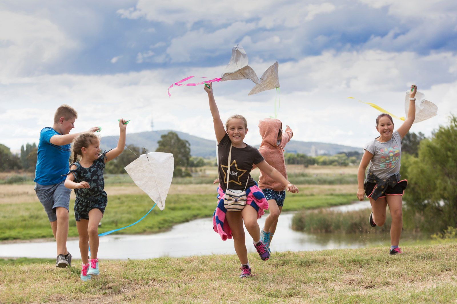 Kids flying kites in front of the wetlands.