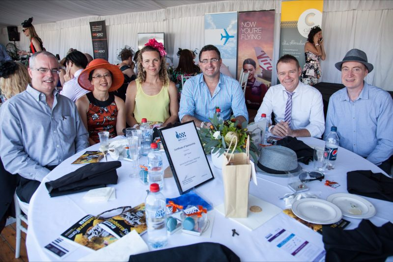 Group of people sitting around a table enjoying Charity Race Day
