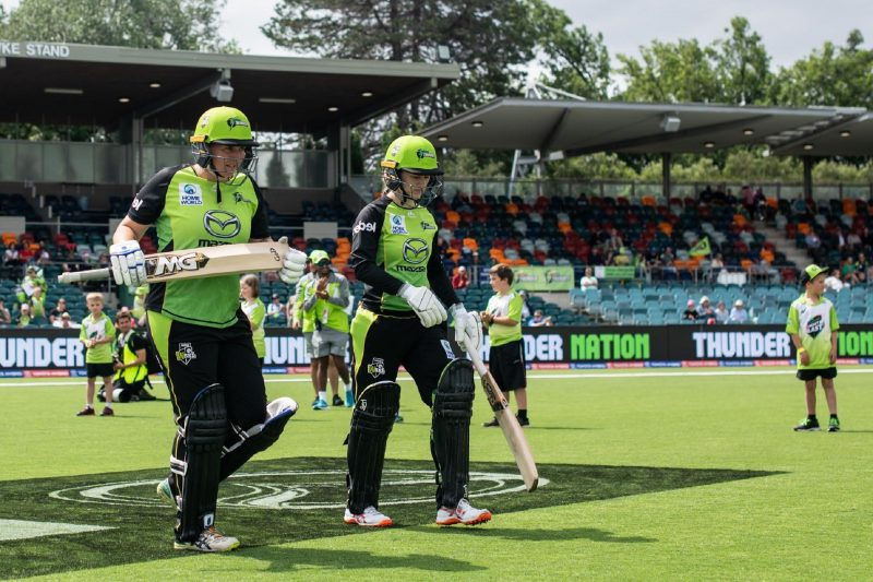 Cricketers walking onto pitch