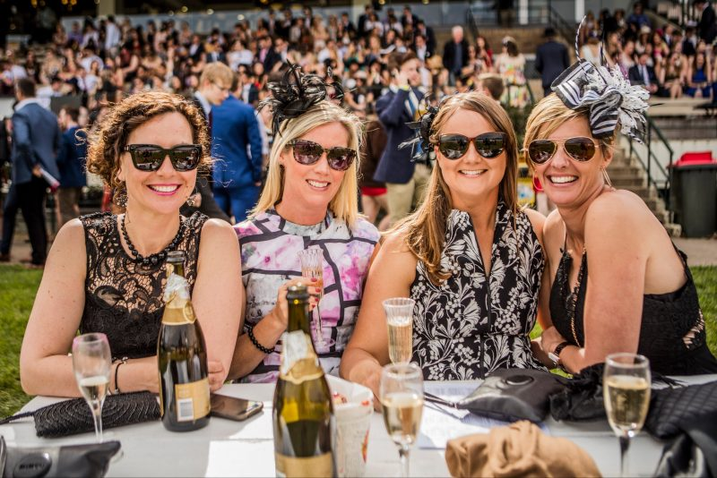 Four ladies dressed for the races enjoying champagne