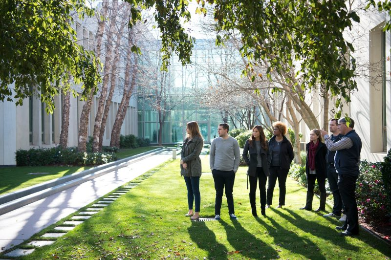 A gardener stands with a group of visitors and points at the trees, explaining the landscape.