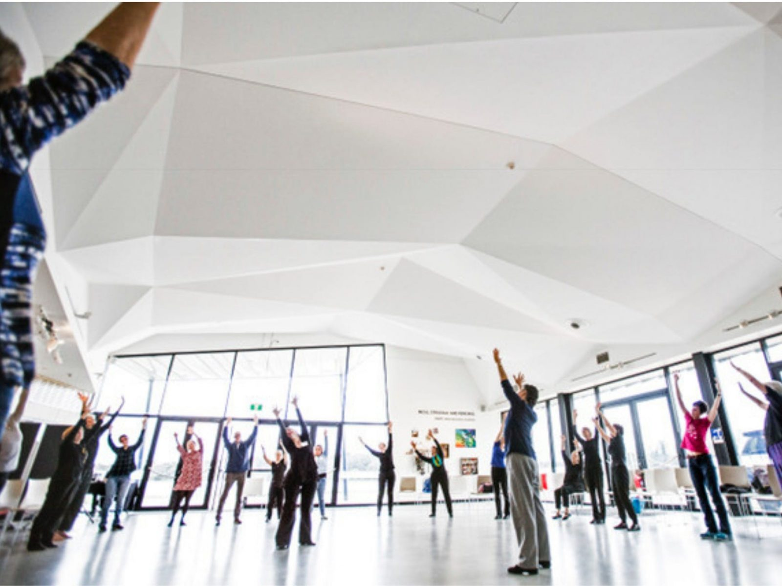 Lots of people stand with their hands raised to the ceiling of Belconnen Arts Centre