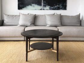 Black oak coffee table, grey modular sofa and enamel glass art.