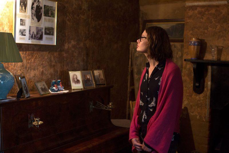 Dark living room at Mugga depicting lady lookin at old photos in wall and piano top