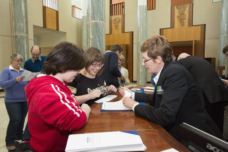 Image of a Visitor Services Officer assisting visitors to Parliament House