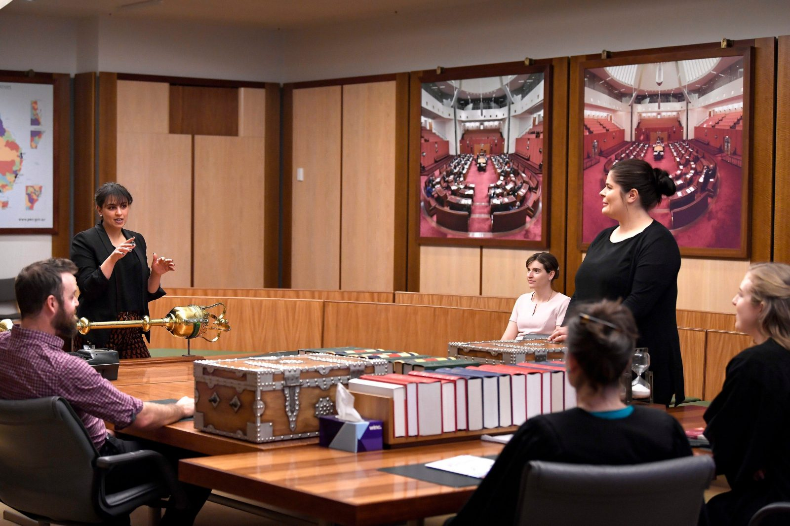 A Parliamentary Educator addresses a group sat at a table. A woman stands as the Prime Minister.