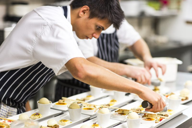 Chefs put finishing touches on dishes in the kitchen