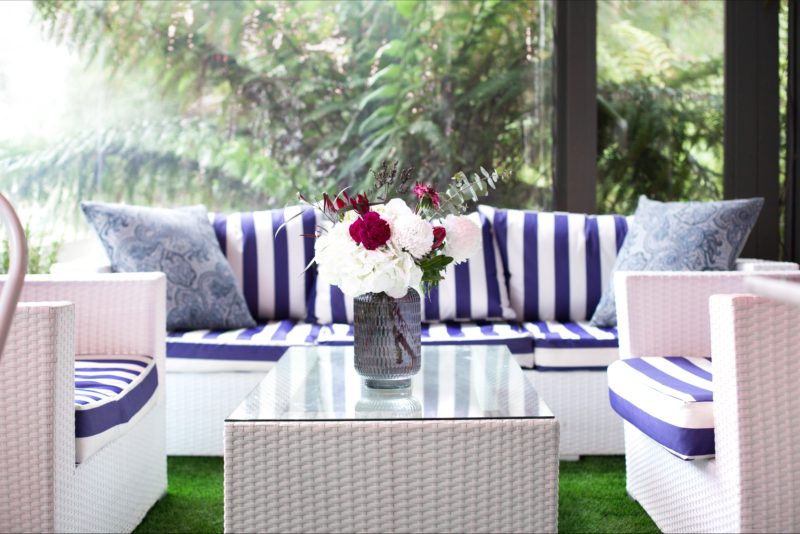 Fresh blue and white furniture by a window overlooking the rainforest garden