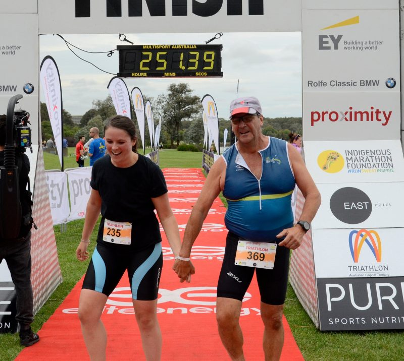 Man and woman hold hands as they cross the finish line